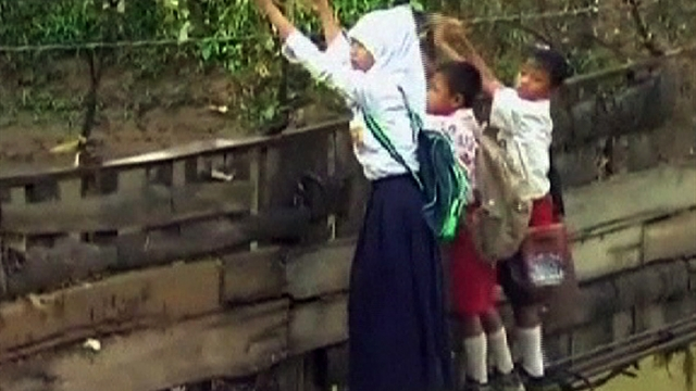 Indonesian students cross collapsed bridge